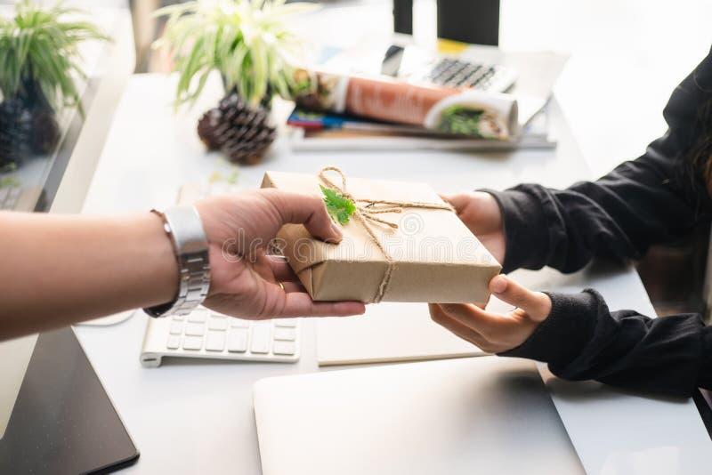 O homem da mão que guarda um papel envolvido caixa de presente do ofício com a fita para a mulher de negócio bonita, sente da fel fotos de stock royalty free