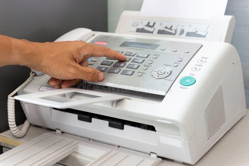 O homem da m?o est? usando um fax no escrit?rio imagens de stock