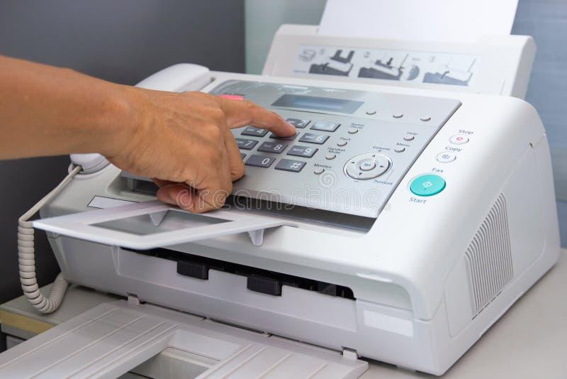 O homem da m?o est? usando um fax no escrit?rio foto de stock
