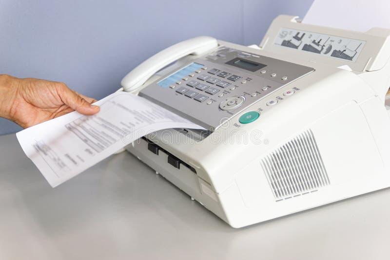 O homem da m?o est? usando um fax no escrit?rio fotos de stock royalty free