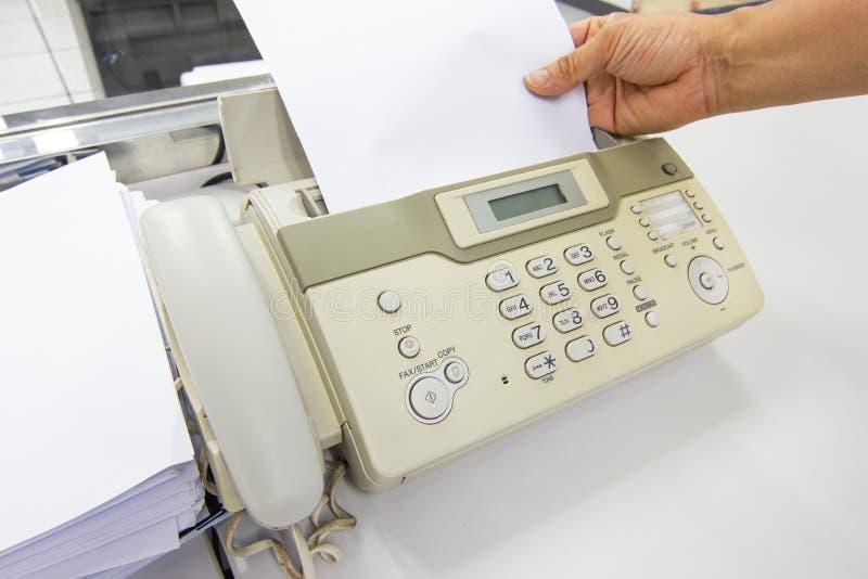 O homem da m?o est? usando um fax no escrit?rio fotografia de stock