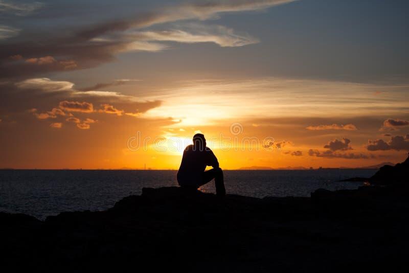O homem da silhueta senta-se em um penhasco imagens de stock royalty free