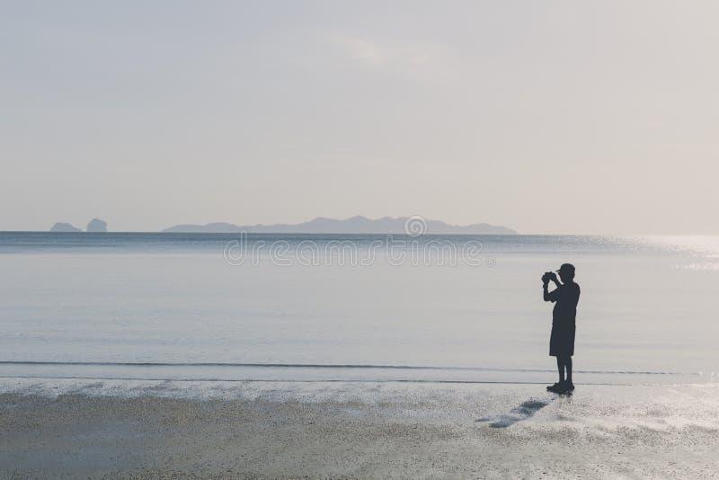 O homem da silhueta toma uma foto na praia fotografia de stock royalty free