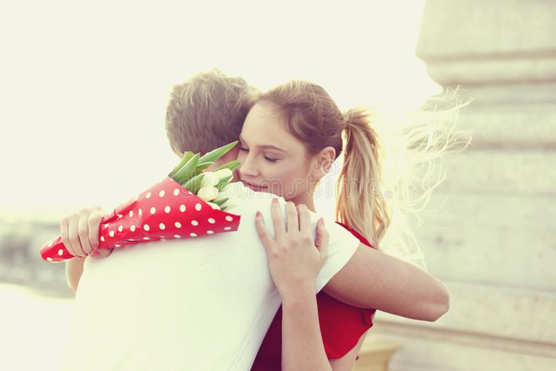 O homem de abraço da mulher loura nova nos olhos da data fechou-se imagem de stock