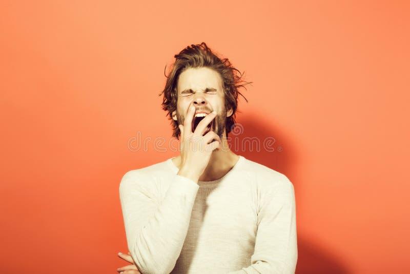 o homem de bocejo sonolento com cabelo uncombed longo, manhã acorda foto de stock