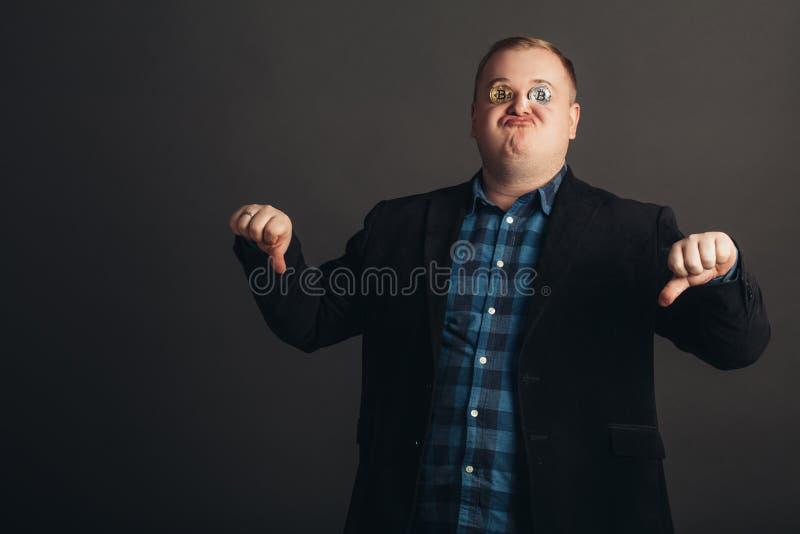 O homem de comemoração gordo faz a cara louca amante louco do bitcoin com a moeda dourada pelos olhos fotografia de stock