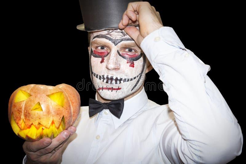 O homem de Dia das Bruxas com composição guarda a abóbora amarela no fundo preto Fundo do partido de Dia das Bruxas fotos de stock