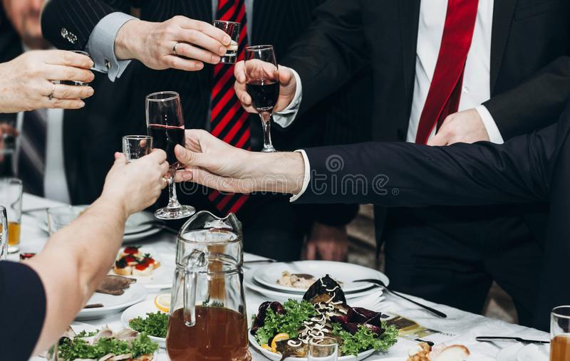O homem de empresa que brinda na tabela do partido de jantar entrega clos imagem de stock