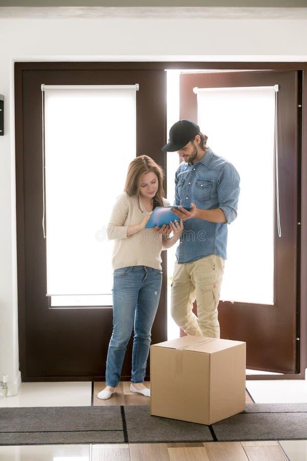O homem de entrega traz um pacote à mulher do cliente foto de stock