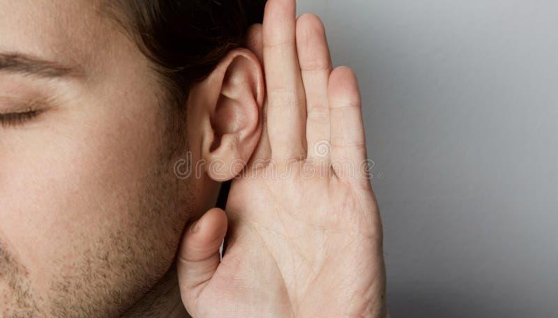 O homem de escuta guarda sua mão perto de sua orelha sobre o fundo cinzento fotos de stock