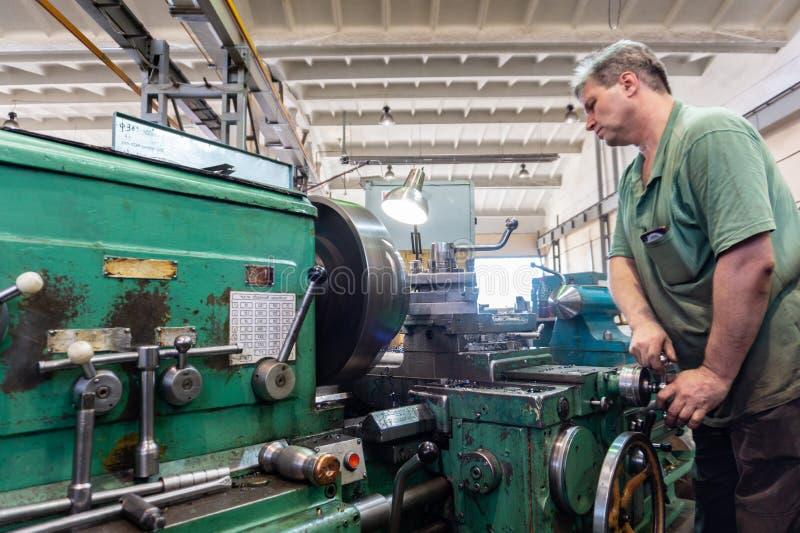 O homem de funcionamento controla o equipamento da máquina de corte Trabalho de giro na produção foto de stock