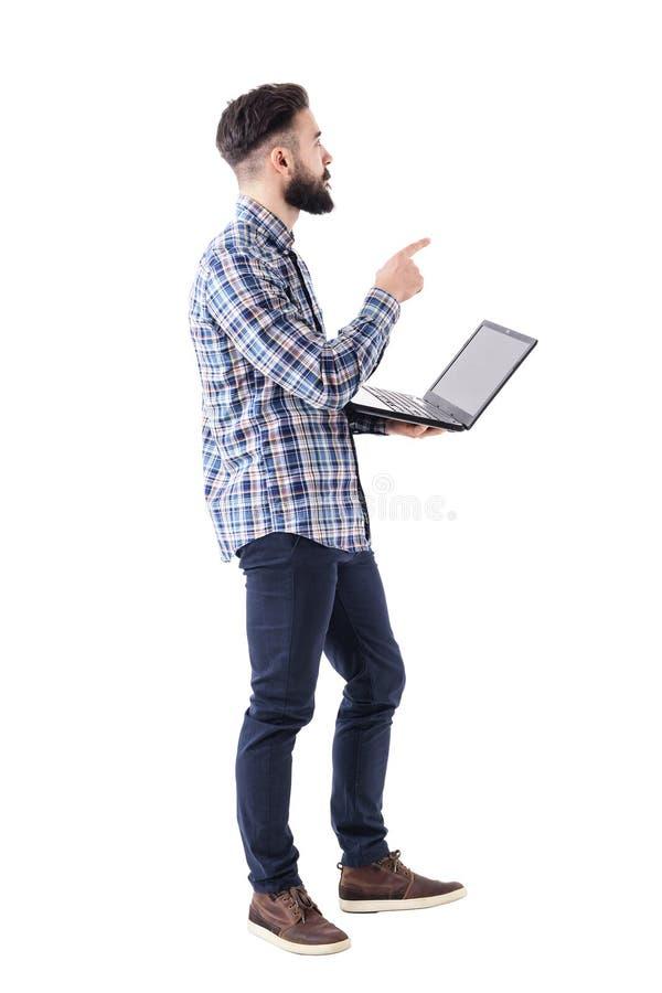 O homem de negócio à moda adulto novo com portátil que aponta o dedo na apresentação olha acima fotografia de stock