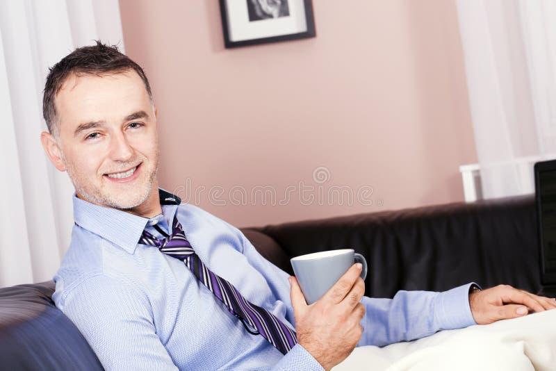 O homem de negócio alegre, considerável em casa. fotografia de stock