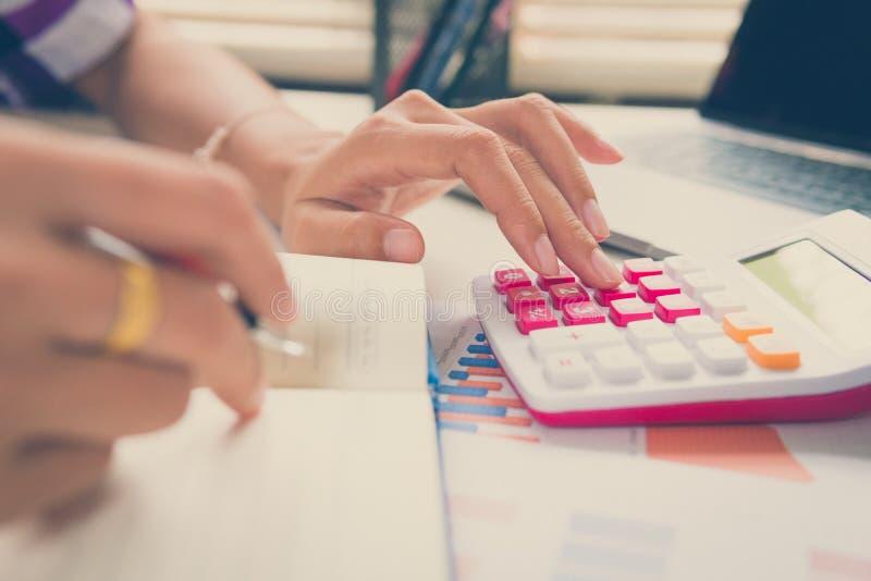 O homem de negócio calcula sobre o custo e finança fazer no escritório fotografia de stock