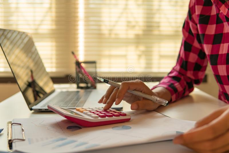 O homem de negócio calcula sobre o custo e finança fazer no escritório fotografia de stock royalty free