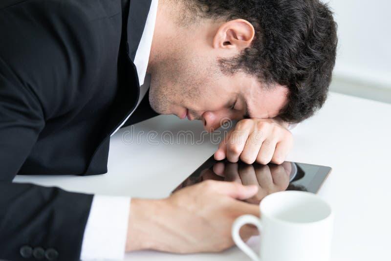 O homem de negócio cansado cai adormecido na tabela imagens de stock