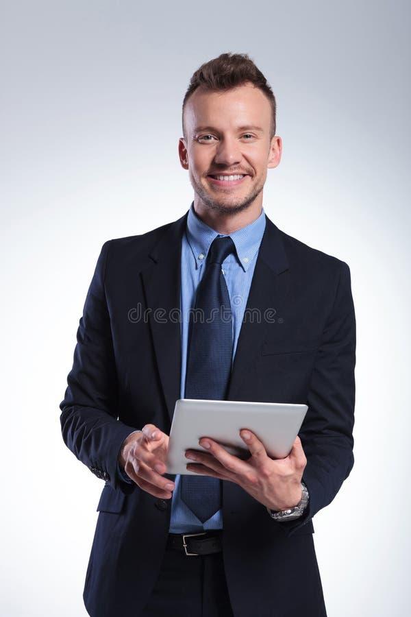 O homem de negócio com tabuleta sorri em você imagem de stock