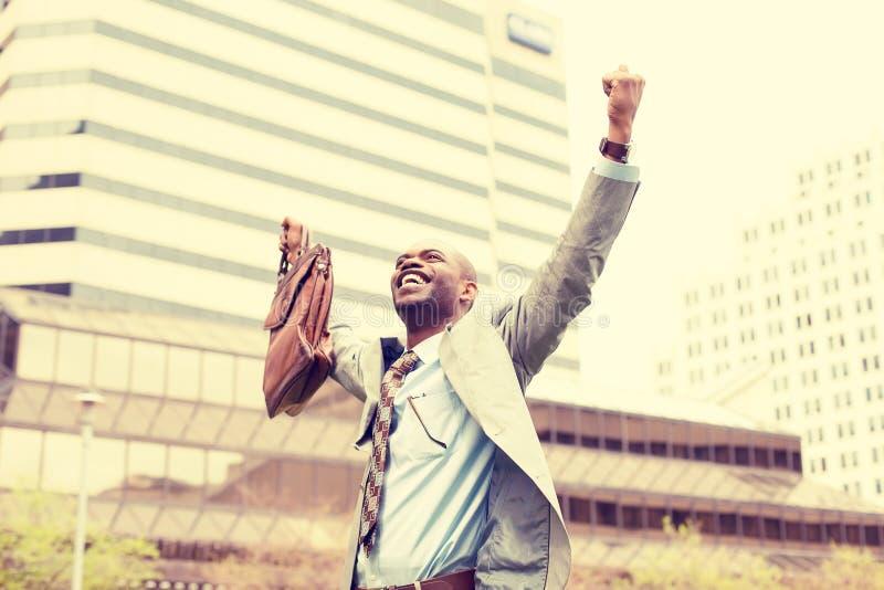 O homem de negócio considerável novo comemora os braços do sucesso da liberdade aumentados imagem de stock