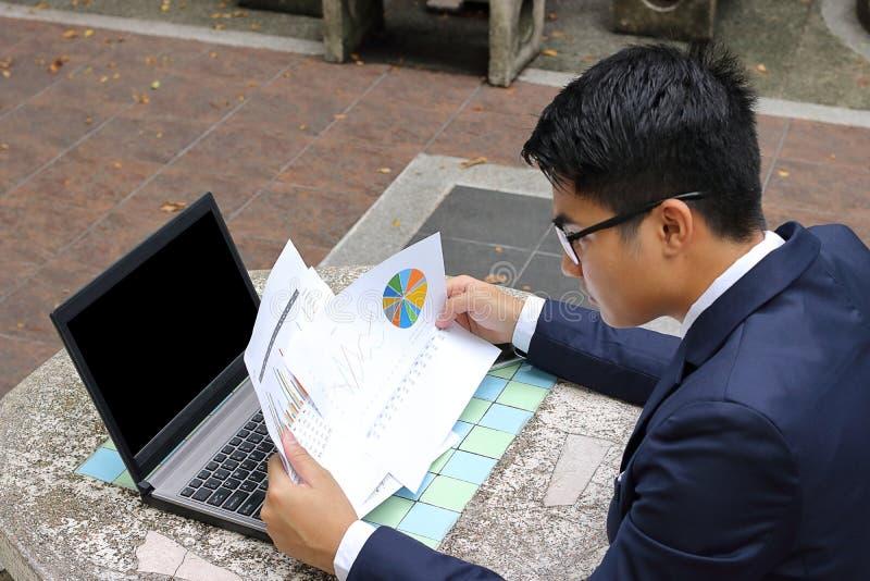 O homem de negócio considerável novo está analisando cartas financeiras e os originais contra o portátil no público fora estacion fotografia de stock royalty free