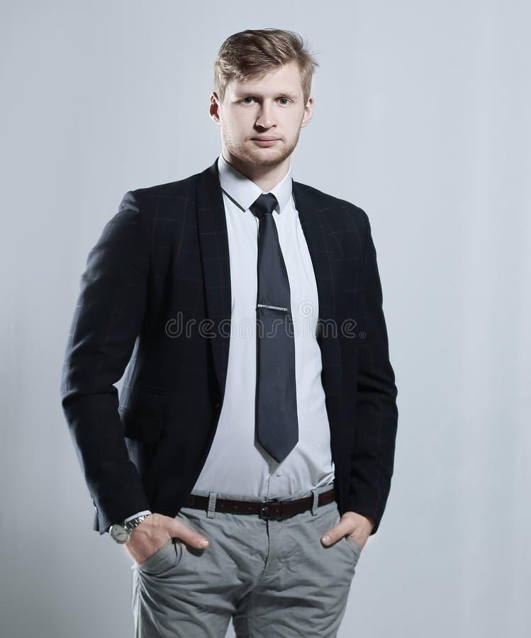 O homem de negócio criativo está com suas mãos em seus bolsos Isolado no fundo cinzento fotografia de stock royalty free