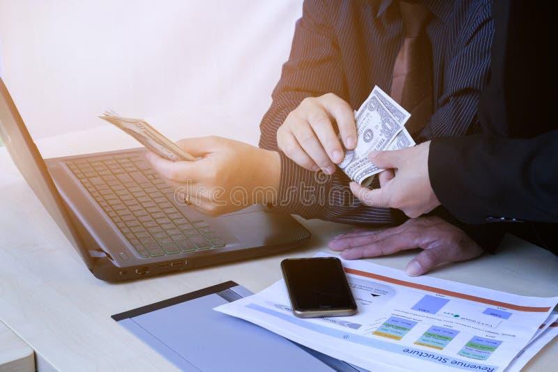 O homem de negócio dá o dinheiro no escritório imagens de stock