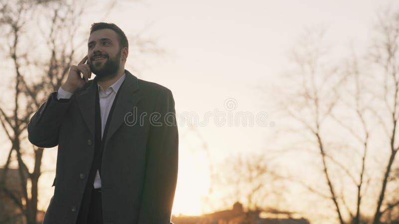 O homem de negócio farpado novo no revestimento que fala no smartphone e que faz trata na rua a luz solar backlit na noite fotos de stock