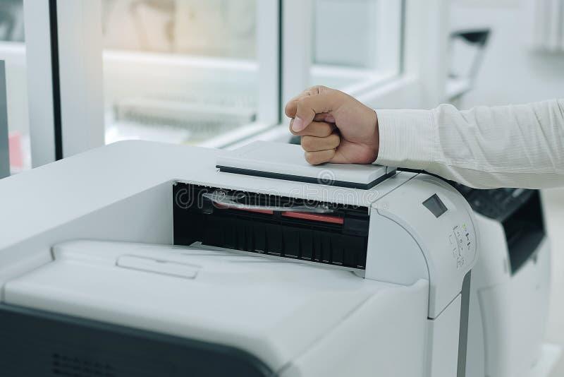 o homem de negócio irritado bate seu punho no varredor de impressora foto de stock