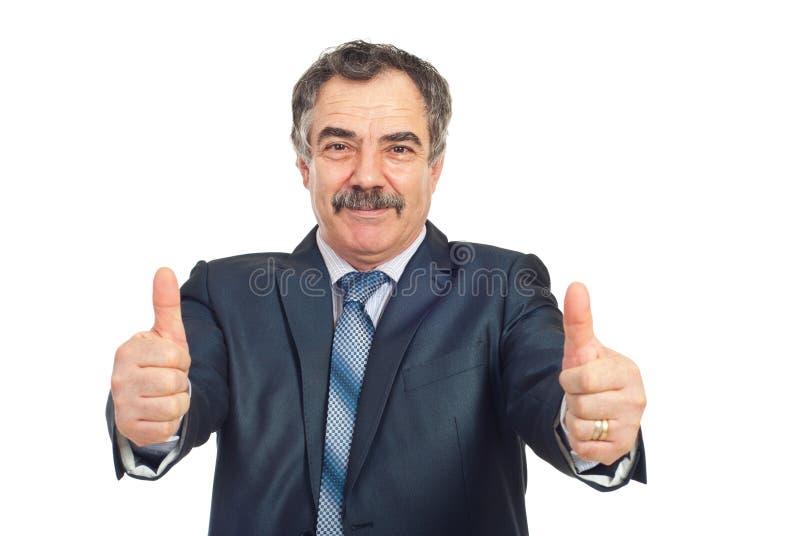 O homem de negócio maduro bem sucedido dá os polegares imagens de stock
