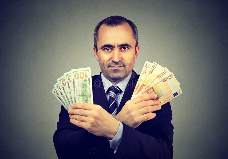 O homem de negócio maduro com euro e o dólar descontam cédulas fotos de stock royalty free