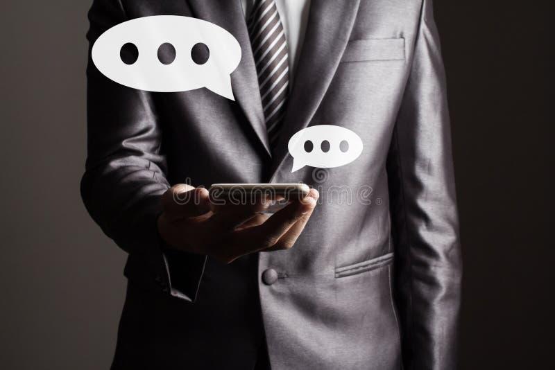 O homem de negócio no terno cinzento que guarda conceito social tocante da tecnologia dos meios da tabuleta fotografia de stock royalty free