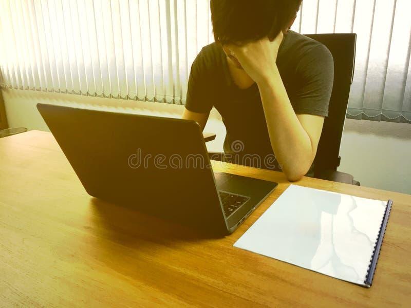 O homem de negócio novo guarda a cabeça com mão durante o trabalho no escritório fotos de stock