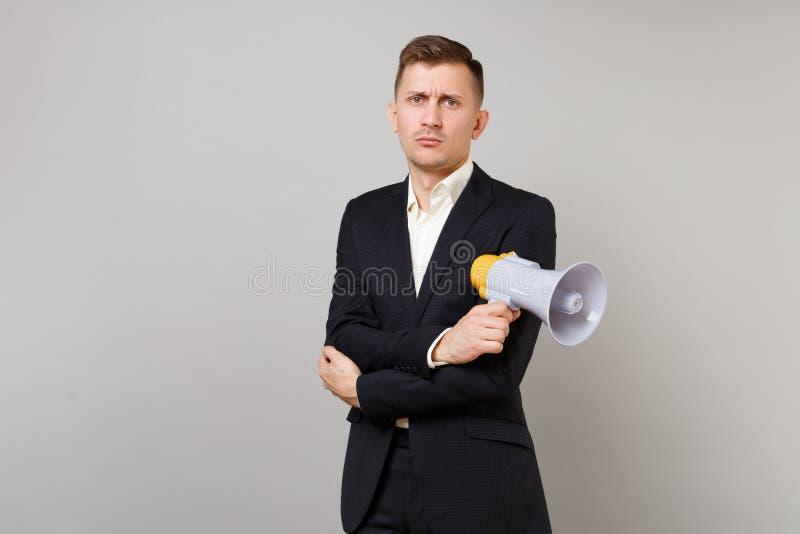 O homem de negócio novo indiferente no terno preto clássico, camisa que guarda as mãos com megafone dobrou-se isolado no cinza imagens de stock royalty free