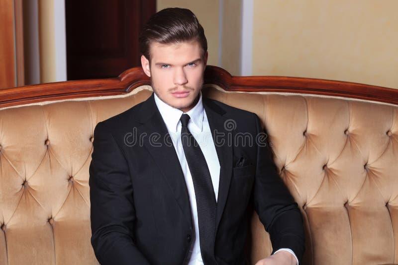 O homem de negócio novo senta-se no sofá retro imagens de stock