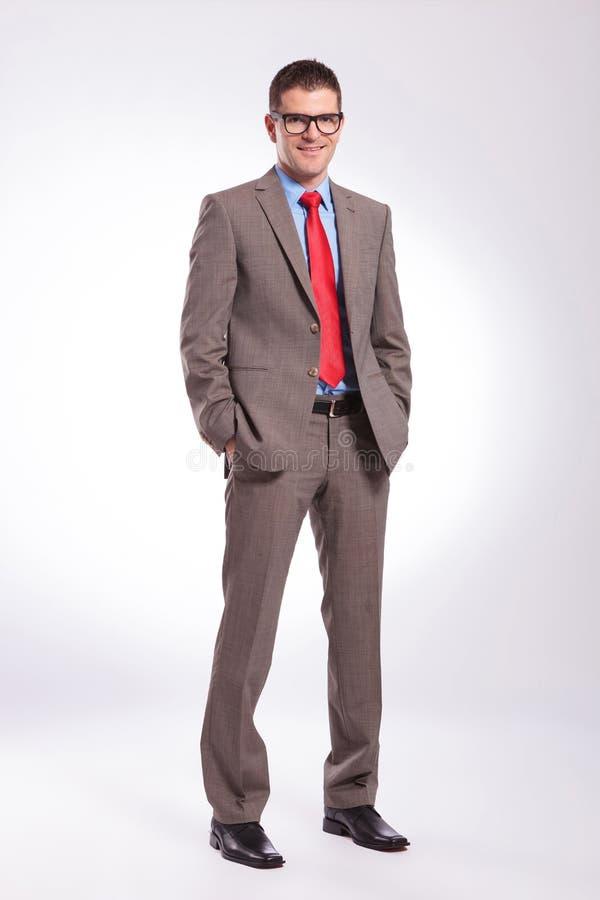 O homem de negócio novo sorri com ambas as mãos em uns bolsos foto de stock royalty free