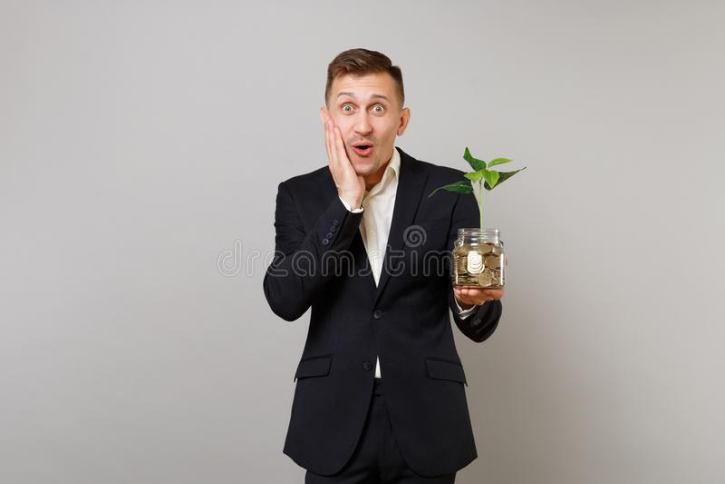 O homem de negócio novo surpreendido pôs a mão sobre o mordente que guarda moedas de ouro da pilha no frasco de vidro com o broto imagem de stock