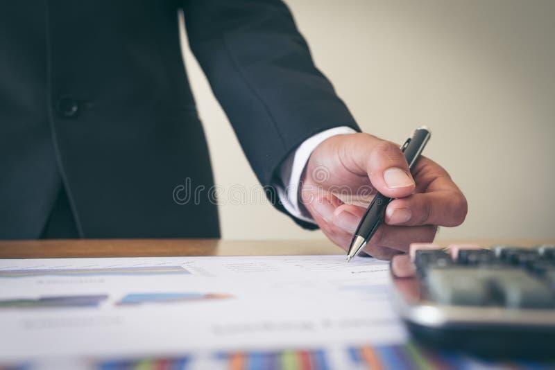 O homem de negócio que analisam o gráfico e a carta documentam o relatório imagem de stock royalty free