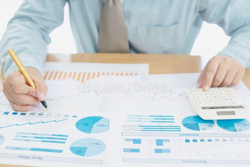 O homem de negócio que usa o funcionamento da calculadora no escritório com relatórios documenta financeiro fotos de stock royalty free