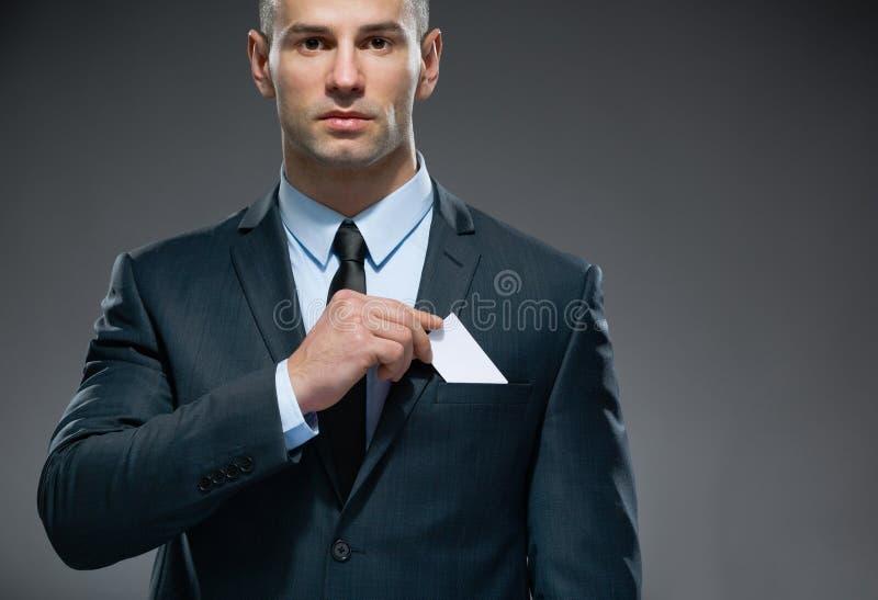 O homem de negócio remove o cartão branco do bolso foto de stock royalty free