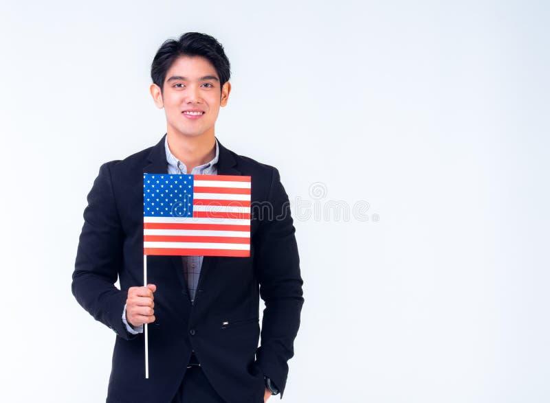 o homem de neg?cio 20s est? guardando a bandeira americana com o fundo branco foto de stock