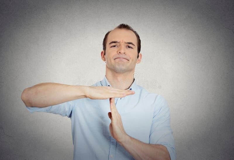O homem de negócio seguro de Erious que mostra o tempo para fora gesticula imagem de stock