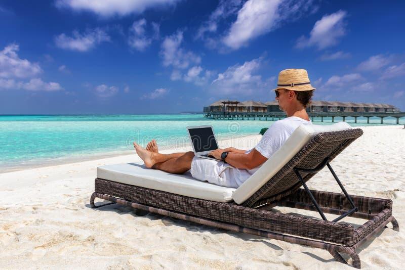 O homem de negócio senta-se em uma praia tropical com seus portátil e trabalhos fotografia de stock royalty free