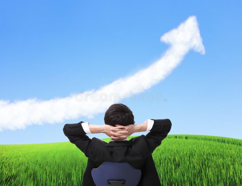 O homem de negócio senta-se na cadeira e olha-se a nuvem do crescimento imagens de stock