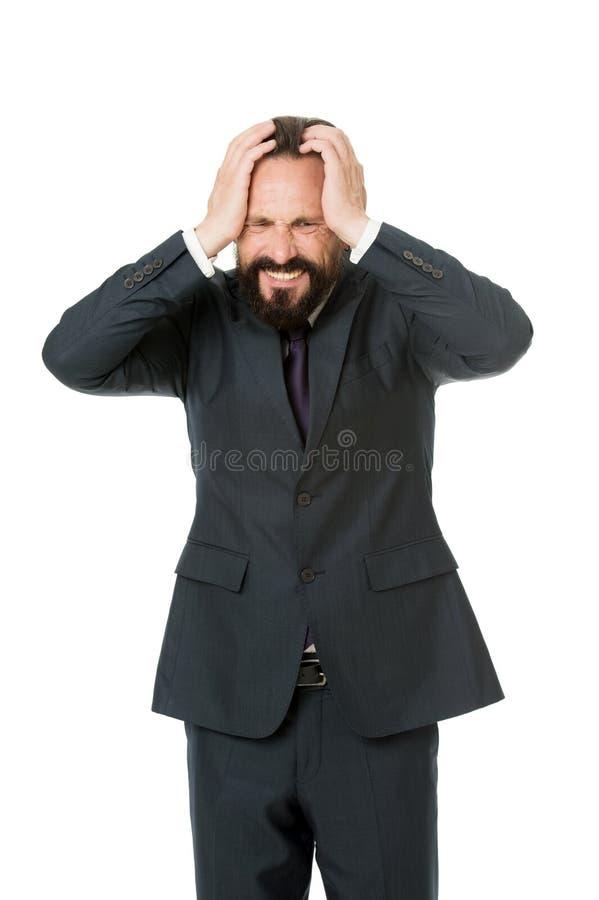 O homem de negócio sofrer a cabeça da mão da posse da dor de cabeça quando o fundo branco do suporte Dia fatigante da dor de cabe imagens de stock