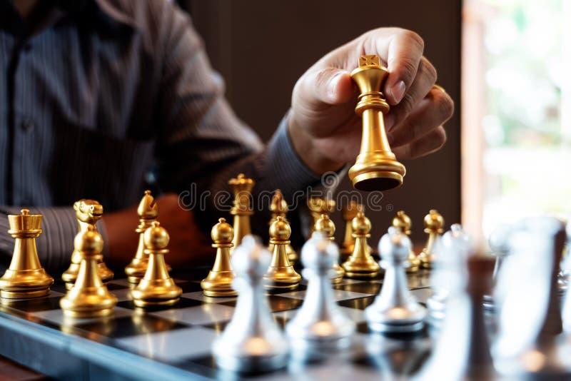 O homem de negócio toma uma figura checkmate no jogo de mesa da xadrez - conceito do rei do sucesso da estratégia, da gestão ou d fotografia de stock royalty free