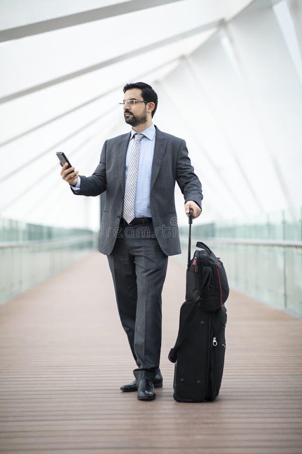 O homem de negócios árabe com sua mala de viagem que olha athis telefona foto de stock royalty free