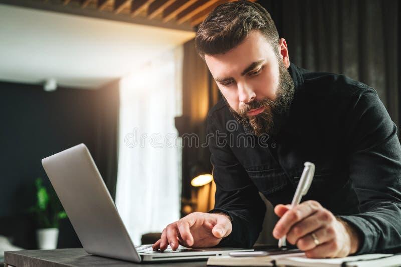 O homem de negócios é o computador próximo ereto, funcionamento no portátil, fazendo anotações no caderno Observação do homem web imagem de stock