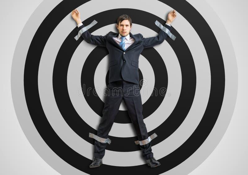 O homem de negócios é gravado ao alvo com fita adesiva foto de stock