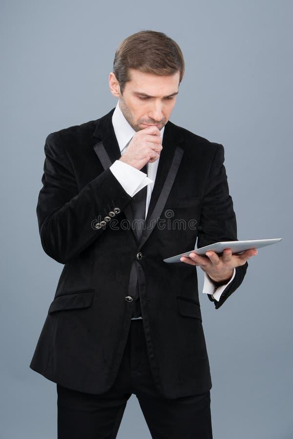O homem de negócios é intrigado pela notícia que está lendo em seu PC da tabuleta fotos de stock
