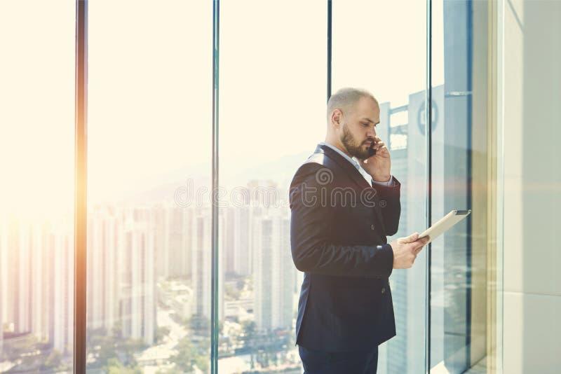 O homem de negócios é janela próxima ereta com espaço da cópia fotografia de stock