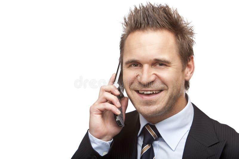 O homem de negócios é sorrisos felizes no telefone fotografia de stock